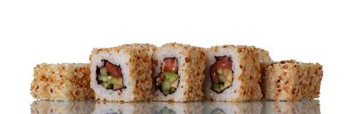 Petits pains de sushi asiatiques traditionnels avec des fruits de mer en graines de sésame d'isolement sur le blanc Image stock