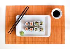 Petits pains de sushi délicieux du plat blanc avec des baguettes Photo libre de droits