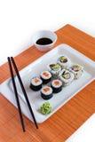 Petits pains de sushi délicieux du plat blanc avec des baguettes Images stock
