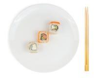 Petits pains de sushi dans le plat avec des baguettes d'isolement Photos stock