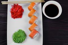 Petits pains de sushi de Philadelphie d'un plat carré blanc avec le wasabi, la sauce de soja et le gingembre Fond en bois foncé photographie stock