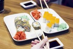 Petits pains de sushi de plat, amis prenant des petits pains Images stock