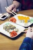 Petits pains de sushi de plat, amis prenant des petits pains en café Photo libre de droits