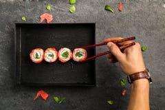Petits pains de sushi qui gardent la main humaine avec des baguettes Photographie stock