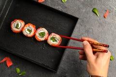 Petits pains de sushi qui gardent la main humaine avec des baguettes Images stock
