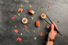 Petits pains de sushi qui gardent la main humaine avec des baguettes photo libre de droits