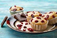 Petits pains de vanille avec les cerises sèches du plat blanc et de la table rustique en bois bleue images stock