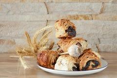 Petits pains doux avec des clous de girofle d'un plat blanc de porcelaine Images stock