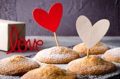 Petits pains doux sur le fond foncé avec le rouge et les coeurs de papier d'emballage, pour le jour du ` s de Valentine Photos stock