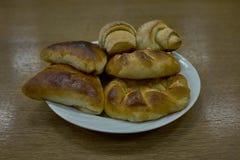 Petits pains et Patty cuits au four frais délicieux d'un plat clair photo stock