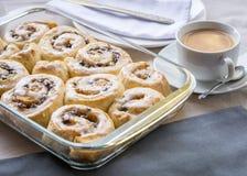 Petits pains faits maison de Chelsea dans un plat en verre avec la tasse de thé Image stock