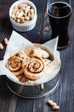 Petits pains frais avec de la cannelle et des écrous sur un fond en bois Photo stock