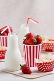 Petits pains, fraises et lait délicieux dans des bouteilles Photo stock