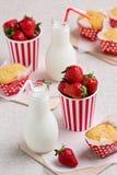 Petits pains, fraises et lait délicieux dans des bouteilles Photographie stock libre de droits