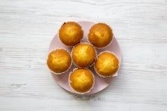 Petits pains savoureux de plat rose au-dessus du fond en bois blanc, Photographie stock