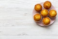 Petits pains savoureux de plat rose au-dessus du fond en bois blanc D'en haut Image libre de droits