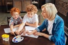 Petits peintres adorables travaillant au nouveau chef d'oeuvre avec la grand-mère Photos libres de droits