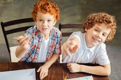 Petits peintres souriant dans l'appareil-photo tout en peignant ensemble Image libre de droits