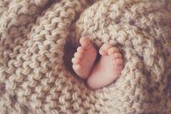 Petits pieds un bébé nouveau-né dans une couverture beige Image stock