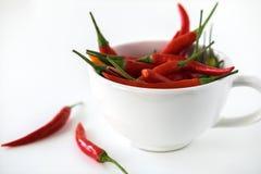 Petits poivrons de piment rouges dans la tasse blanche sur le fond blanc Foyer sélectif Photographie stock