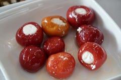 Petits poivrons rouges bourrés du lait caillé dans une cuvette peu profonde Photographie stock libre de droits