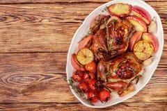 Petits poulets entiers cuits au four avec les pommes, le citron, l'ail, le thym, les tomates et les épices photographie stock