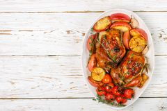 Petits poulets entiers cuits au four avec les pommes, le citron, l'ail, le thym, les tomates et les épices image libre de droits
