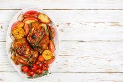 Petits poulets entiers cuits au four avec les pommes, le citron, l'ail, le thym, les tomates et les épices photo stock