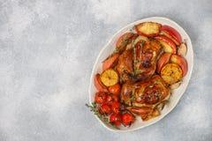 Petits poulets entiers cuits au four avec les pommes, le citron, l'ail, le thym, les tomates et les épices photos libres de droits