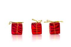 3 petits présents de rouge de Noël sur le fond blanc Image libre de droits