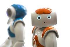 Petits robots avec le visage humain et le corps AI Image stock