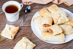 Petits tartes aux pommes ou chiffres d'affaires de pomme avec de la cannelle sur un plat blanc avec la tasse de thé et les pommes Photo libre de droits