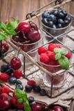 Petits verres de fruit contenant la cerise, la myrtille et rasberry photographie stock