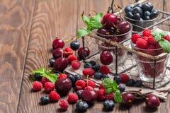 Petits verres de fruit contenant la cerise, la myrtille et rasberry photo stock