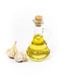 Petróleo da azeitona ou de girassol no frasco e no alho imagem de stock