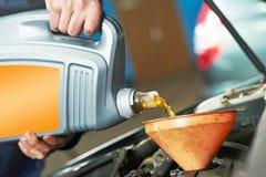Petróleo de derramamento da mão do mecânico do close up no motor do carro Imagens de Stock Royalty Free