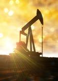 Petróleo pozo contra flama brillante del sol. Imagen de archivo libre de regalías