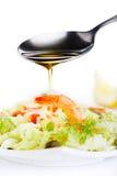 Petróleo verde-oliva de derramamento na salada Fotos de Stock