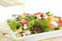 Petróleo verde-oliva de derramamento na salada fresca. Fotografia de Stock Royalty Free