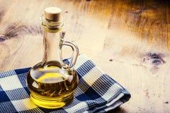 Petróleo verde-oliva Garrafas do pano quadriculado azul do azeite em uma tabela de madeira Imagens de Stock