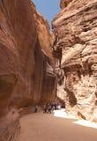 Petra峡谷岩石狭窄的段落的游人在约旦 库存照片
