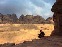 PETRA,约旦, 2011年11月25日:一位警察的剪影全国衣裳的反对岩石背景  图库摄影