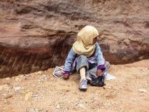PETRA,约旦, 2011年11月25日:卖纪念品的坐的小女孩为游人 免版税库存图片