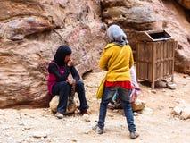 PETRA,约旦:卖纪念品的三个女孩为游人 免版税库存照片