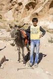 PETRA -约旦2015年12月25日:有他的驴的阿拉伯男孩 免版税库存图片