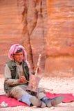 PETRA, JORDÂNIA - 11 DE MARÇO DE 2016: Um músico beduíno que joga e que canta no Siq exterior imagens de stock