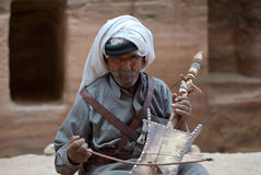 Petra, Jordan. Bedouin man playing traditional instrument Stock Photos