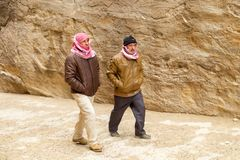 Two bedouins walking in Al Siq passage to ancient Petra town stock photo