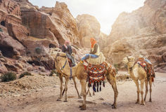 PETRA, JORDAN - NOVEMBER 22, 2007: Unidentified local Bedouin guided on camels near Royal tombs. Royalty Free Stock Images
