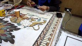 Petra, Jordanië - 2019-04-20 - mozaïek 5 - de kunstenaars lijmt stukken voor leeuwplaque stock videobeelden